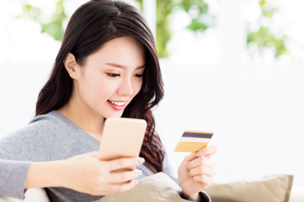 Image of young woman shopping an eCommerce site using Mobile phone and credit card. eCommerce has changed customer behavior both online and off.