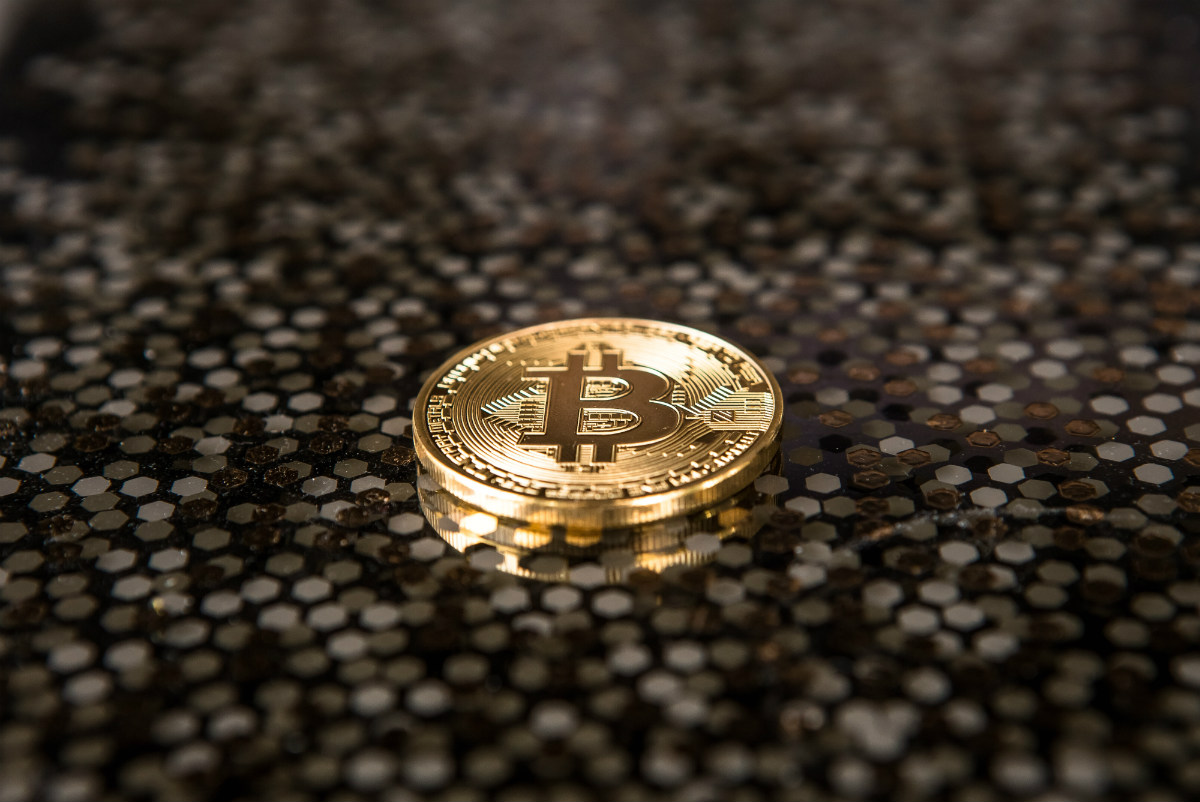 a gold coin with bitcoin symbol on it representing cryptocurrency