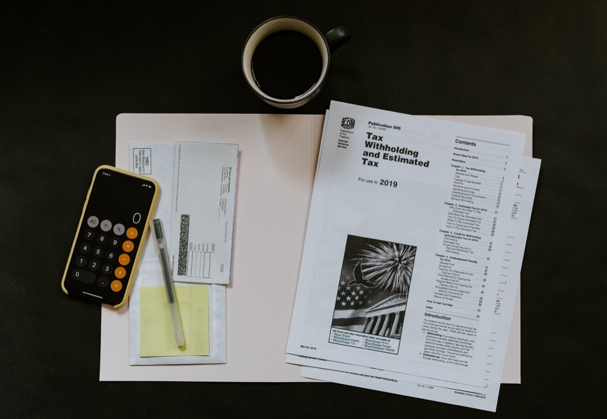 Tax documents, a calculator and a mug of coffee; eCommerce taxes concept