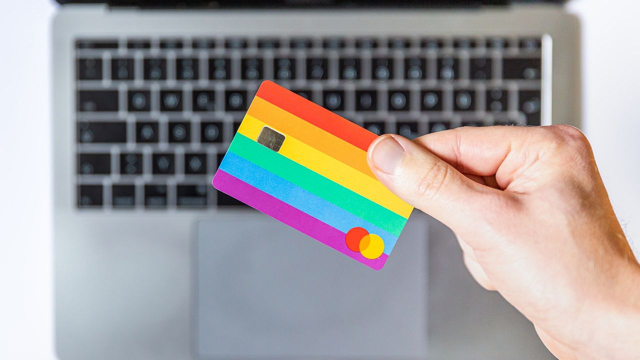 Hand holding a rainbow flag credit card; trust signals concept