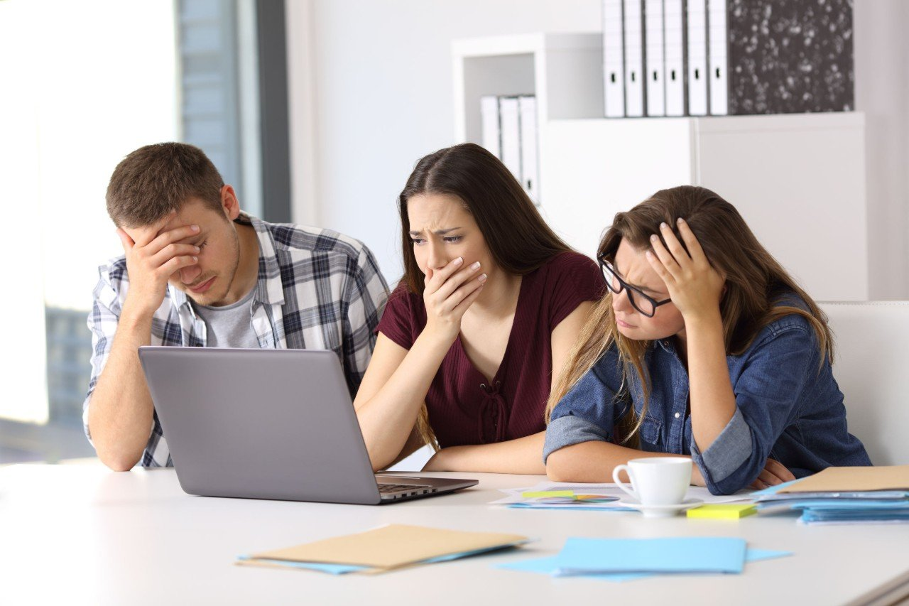 Three customers frown at a laptop; concept: eCommerce fraud is part and parcel of selling online.