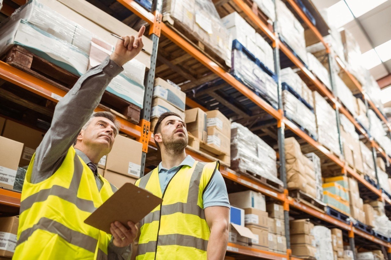 two warehouse works discuss, while pointing at boxes; eCommerce fulfilment concept