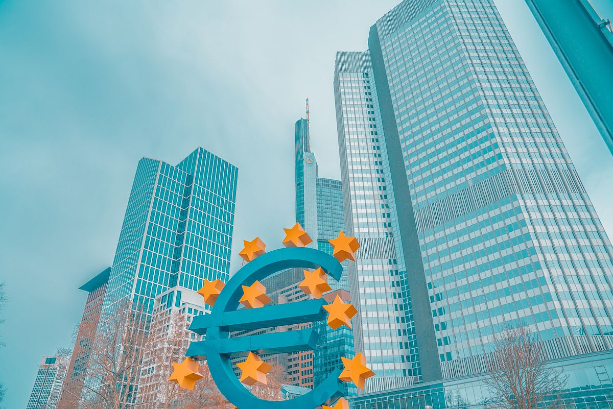 sculpture of the euro symbol in front of glass office buildings; cross-border eCommerce concept