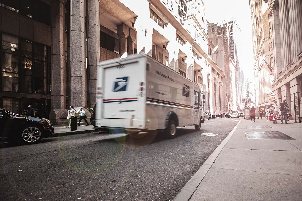 USPS delivery truck speeds through a busy city; carbon offsetting for eCommerce concept