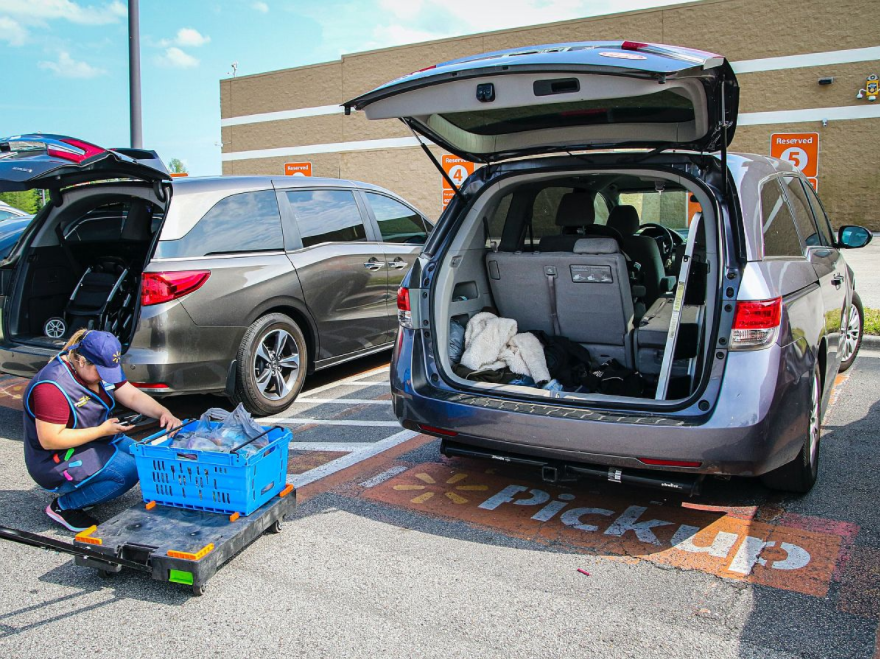 Image of grocery store employee packing a customer's car with an online order