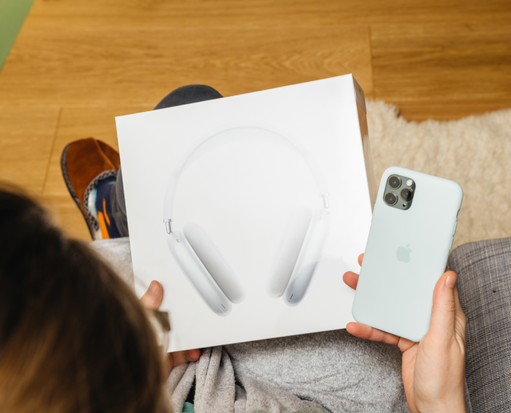 Image of consumer holding Apple AirPods Max over-ear headphones in Apple box. next to Apple iPhone