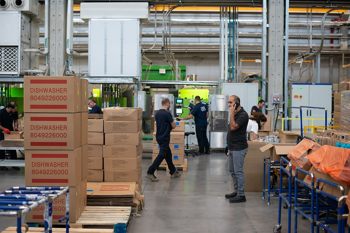 Busy warehouse with stacks of boxes and workers in motion; third-party logistics (3PL) partnership concept