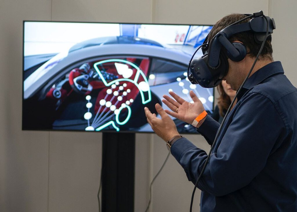 Photo of Man Wearing VR headset in front of television monitor.