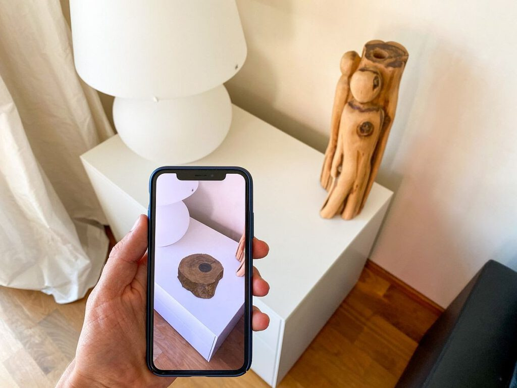 image of person holding mobile phone up to nightstand as they use VR virtaul try on tool to visualize home decor item on nightstand.