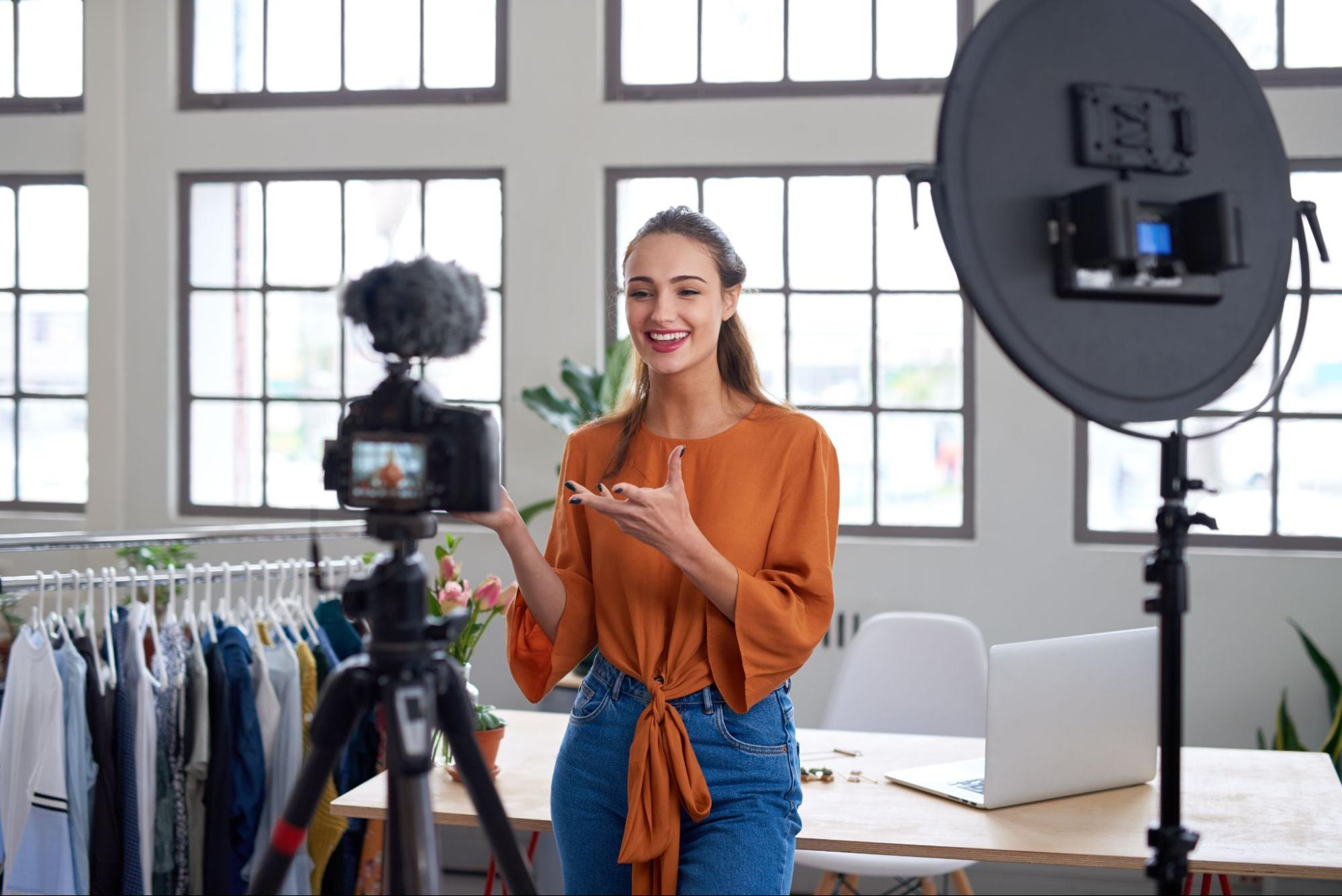 photo of woman livestreaming in modern apartment showcasing trendy clothes